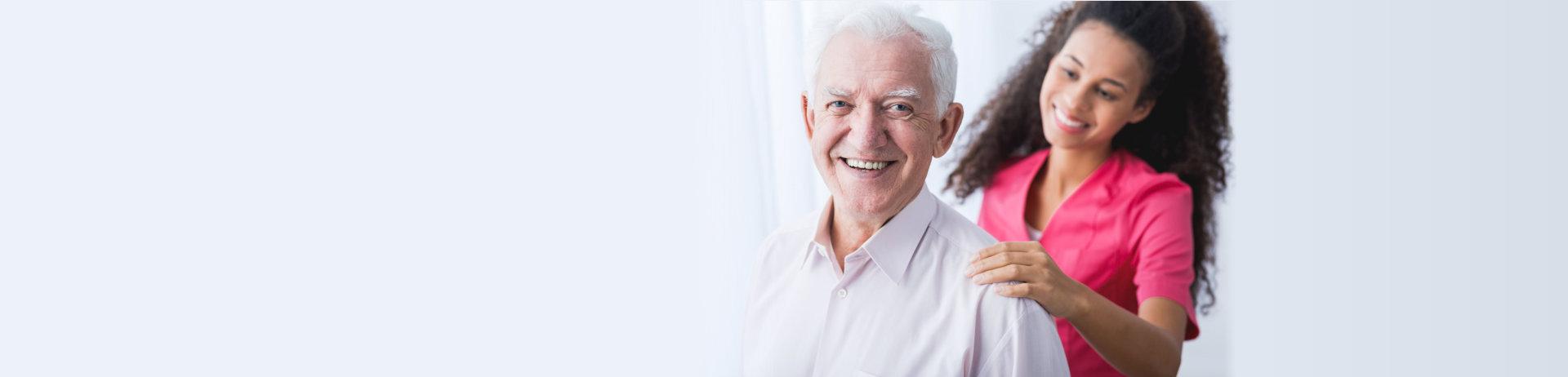 senior man smiling at his caregiver