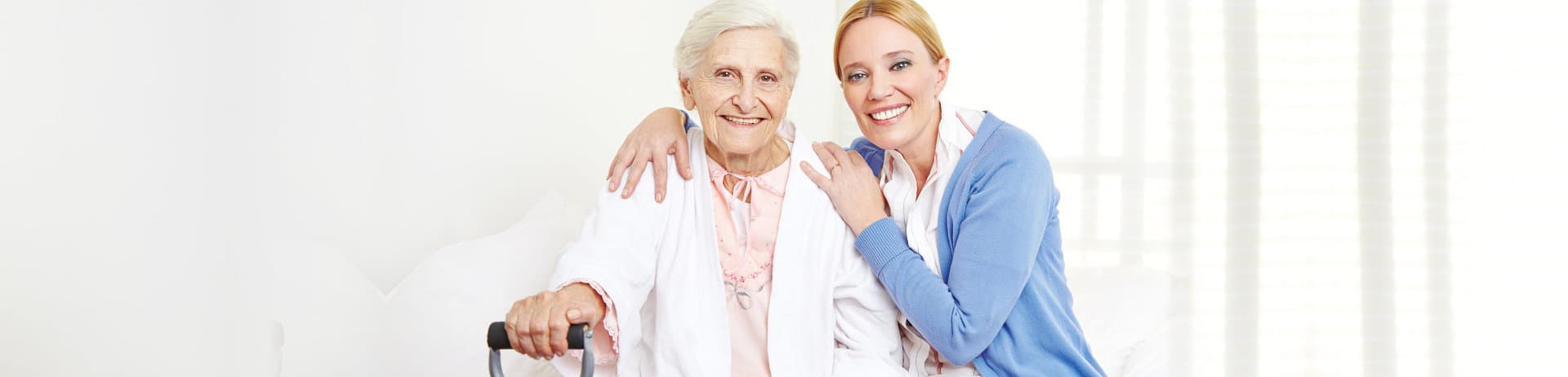 senior woman smiling with her caregiver